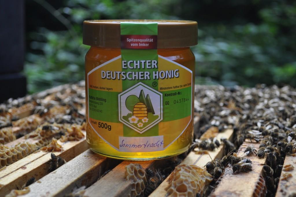 Ein starkes Bienenvolk sitzt dicht auf den Rähmchen der zweiten Zarge, so wie es hinter dem Honigglas zu sehen ist.