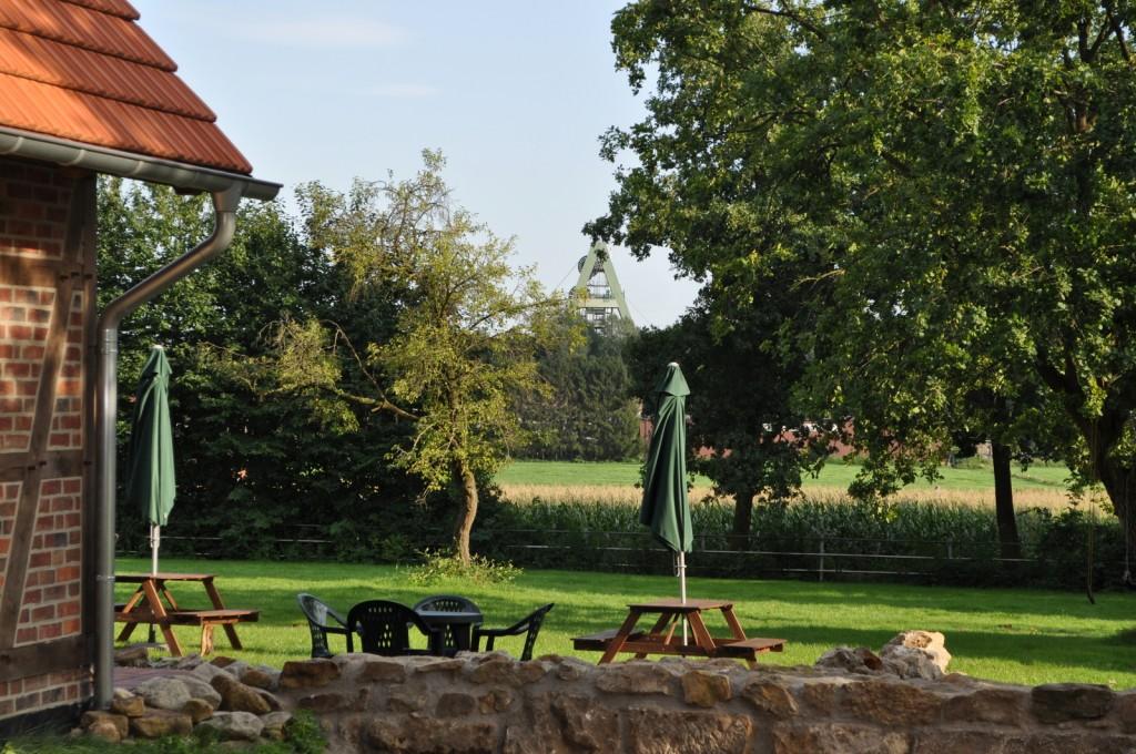 Hier kann man die Seele baumeln lassen: gemütlicher Sitzplatz fast auf der Wiese, umgeben von Eichen mit Blick auf Auguste Viktoria.